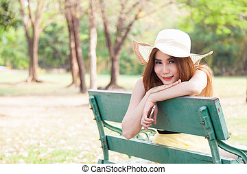 Asian women sitting on a bench in the park.