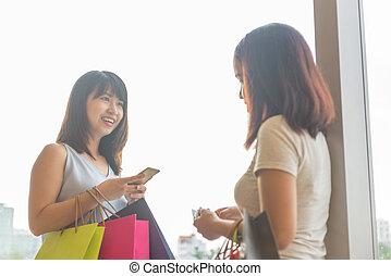 Asian women talking in the mall