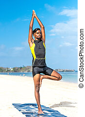 Asian yoga man practice yoga on the beach with a clear blue sky background. Yogi on the tropical beach of Bali island, Indonesia.