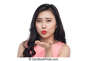 Asian young beautiful woman in pink dress blowing over white.