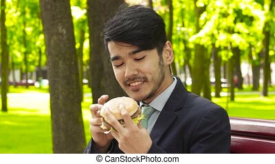 Asian young businessman is sitting on bench in park and...