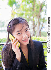 Asian young businesswomen Are using the phone to communicate