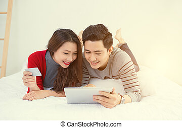 Asian young couple shopping online at home
