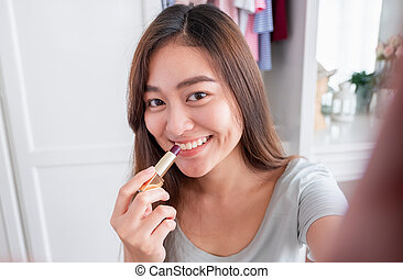 Asian young female blogger recording selfie vlog video with makeup lipstick cosmetic at home online. Influencer on social media concept