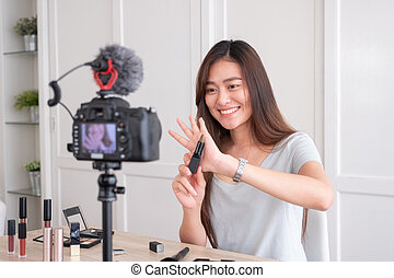 Asian young female blogger recording vlog video with makeup cosmetic at home online influencer on social media concept.live streaming viral .