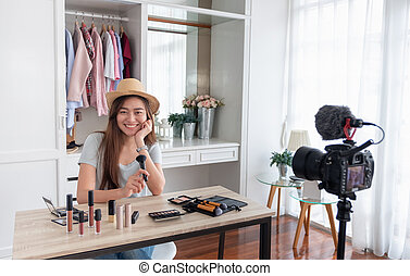 Asian young female blogger recording vlog video with makeup ...