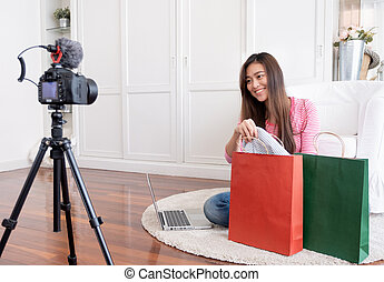 Asian young female blogger recording vlog video with review cloths T-shirt at home online influencer on social media concept.live streaming viral.