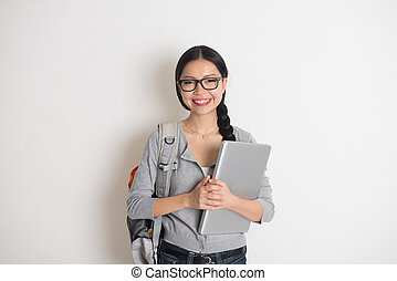 asian young female student with laptop and plain background