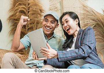 asian young man and woman are excited to see the high sales of handicrafts on digital tablets