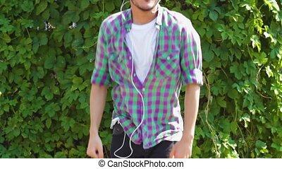 Asian young man in earphones dancing in park - Asian student...