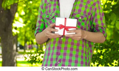 Asian young man opening gift in park. Closeup - Handsome...