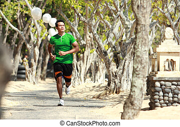 Asian young man running on the alley with trees alongside, Sport concept