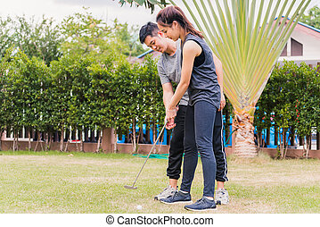young man support teaching training woman to play perfect golf while standing together