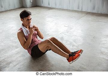 man workout doing sit up - asian young man workout doing sit...