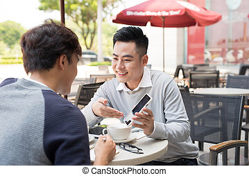 Asian young men enjoying watching on mobile phone together in cafe with coffee on the table.