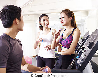 asian young people chatting in gym