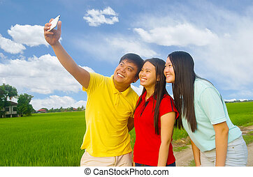 Asian young teenager - happy young teenager taking selfie in...