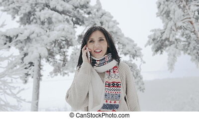 Asian young woman dressed in a warm sweater and warm scarf fun talking on the phone in the wild on a frosty winter day and stepping forward