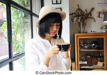 Asian young woman drinking coffee portrait with in coffee shop