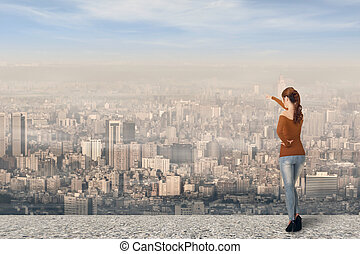 Asian young woman point somewhere over the city, full length portrait.