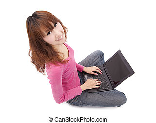 Asian young woman sitting on floor with a laptop