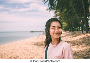 Asian young woman smiling with wind blowing her hair