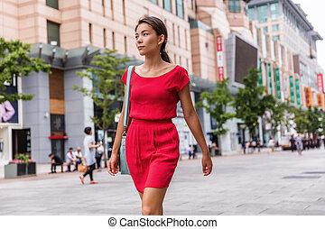 Asian young woman walking alone in city street relaxing enjoying modern Beijing travel lifestyle. Mixed race chinese caucasian girl commuting outside.