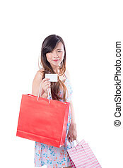 Asian young woman with red dress holding a credit card and paper bag paper isolated on white background.