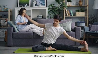 asiatique, homme yoga, jeune, maison, sien, épouse, sofa, portable utilisation, pratiquant, quoique