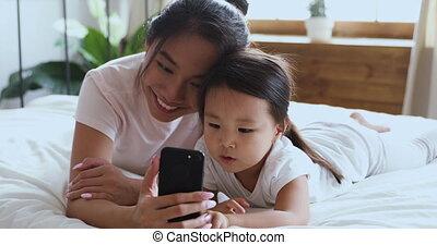 asiatique, mère, fille, utilisation, heureux, lit, smartphone, enfant