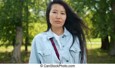 asiatique, sérieux, dehors, debout, regarder, parc, appareil photo, vert, dame