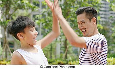 asiatisch, vater & sohn, geben, a, hoch fünf, nach, spielergebnis, draußen, in, morgen