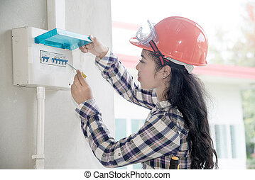 asiatisk kvinna, elektriker, eller, ingenjör, kontroll, eller, syna, elektrisk, system, strömbrytare, på, driva, fördelning, panel, hos, home.
