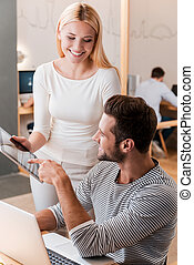 Asking for an expert advice. Cheerful young man and woman discussing something and looking at digital tablet together while their colleagues working in the background