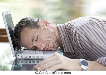 Asleep at work - man sleeping on his laptop