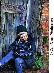 Elderly woman, sits in an alley in the doorway of an abandoned building.  She is sleeping clutching her black plastic bag of belongings.