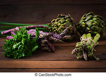Asparagus and artichokes with herbs on a wooden background