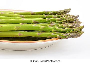 Asparagus - Fresh raw asparagus on rustic plate isolated on...