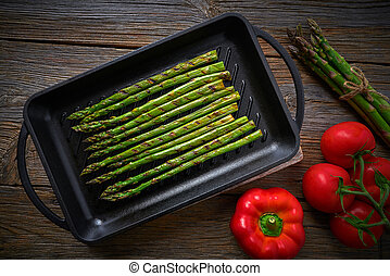 asparagus grilled on cast iron grill pan on wood table with ...