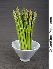 Asparagus in bowl on a black background
