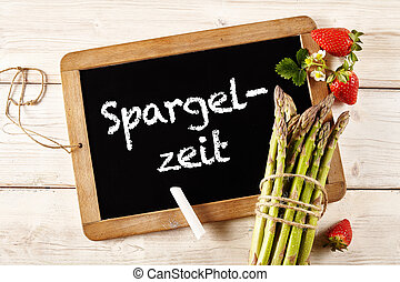 Asparagus in German on chalkboard next to spears