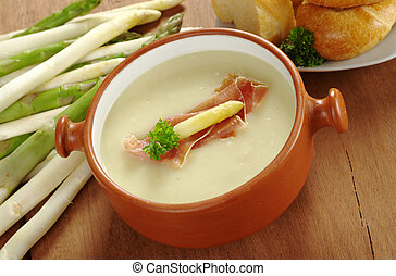 Asparagus soup garnished with ham, asparagus head and...