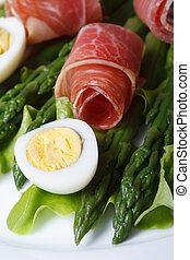 Asparagus with boiled eggs and ham  macro. Vertical