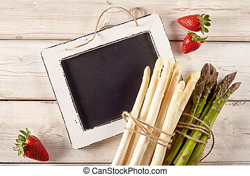 Asparagus with strawberries and chalkboard