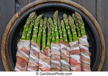 Asparagus wrapped in bacon on the hot pan