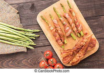 Asparagus wrapped in bacon with tomato on wooden background