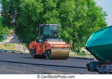 asphalt compactor on the road - Roller machine rolls fresh ...