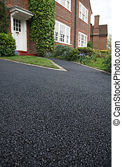 Asphalt drive - New asphalt tarmacadam driveway outside a...