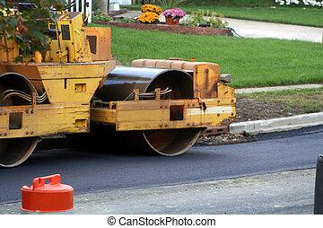 Steamroller flattening hot tar as a new cover finish for an asphalt road.