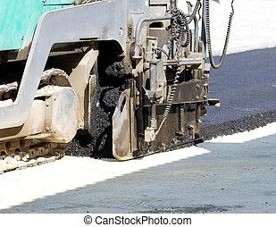 Asphalt finisher machine - Close up of paving machine laying...